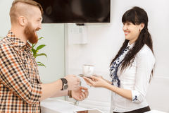 Office manager offering the customer a cup of tea. On reception Royalty Free Stock Photography