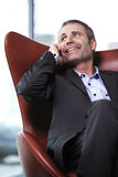 Office manager in red chair talking on cell-phone. Royalty Free Stock Photography