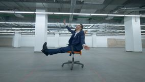 Office manager is riding on a rolling chair across an empty hall. 4K stock footage