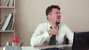 Office manager tired man working on a laptop. He`s hot, his tie`s choking him. He unties his tie stock footage