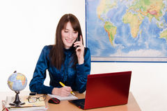 Office manager travel agency on the phone. Young beautiful employee in the office of the travel agency Royalty Free Stock Images