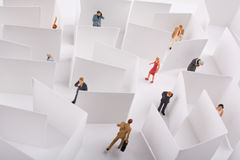 Office Maze Concept. Miniature figures in a maze of white walls Stock Image