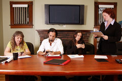 Office meeting. Boss reads assignment while diverse employees are on cellphones royalty free stock photo