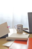 Office at morning. A cup of coffee on desk, with some office equipment, laptop, notes, envelope, document, vertical frame royalty free stock photo