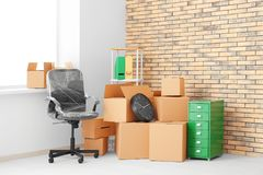 Office move concept. Carton boxes and furniture. In empty room royalty free stock images