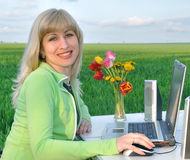 Office on the nature. Lady works on a laptop on the nature Stock Image