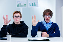Office nerds gesturing prosperity salute. Two male office workers, with a nerdy appearance, gesture the prosperity salute made popular by a well known character royalty free stock photo