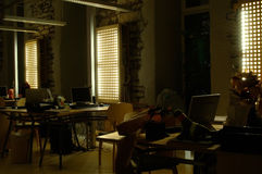 Office at night. Dim view of a modern office at night. Minimal lighting to take the shot, empty workspaces. Some alternative to the common daytime office shots Royalty Free Stock Image