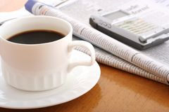 Office objects. Coffee, cellphone and newspaper on work table Royalty Free Stock Photo