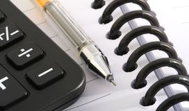 Office objects. Ballpen and calculator on notebook Stock Photos