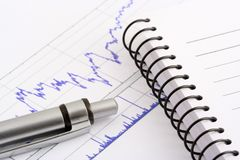 Office objects. Pen and notebook on stock chart Royalty Free Stock Images