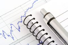 Office objects. Pen and notebook on stock chart Stock Photo