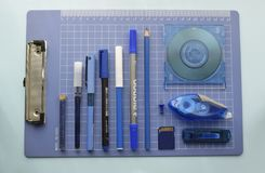 Office objects arranged in blue grid stock image