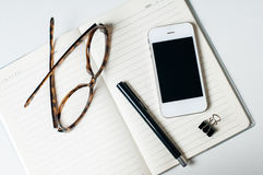 Office objects. Business office objects: smartphone, notebook, glasses and pen on a white background Royalty Free Stock Photography