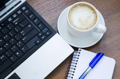 Office objects with laptop, coffee cup and a notebook Stock Photo