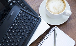 Office objects with laptop, coffee cup and a notebook Royalty Free Stock Photo