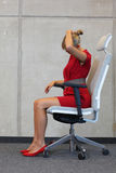 Office occupational disease prevention. Business woman exercising on chair Royalty Free Stock Photography