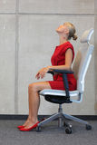 Office occupational disease prevention. Business woman exercising on chair Royalty Free Stock Photos