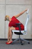 Office occupational disease prevention. Business woman exercising on chair - back view Royalty Free Stock Photo