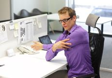 Office occupational disease prevention. Male office worker,exercising during work with tablet in at his desk - occupational disease prevention Royalty Free Stock Photo