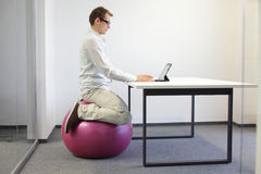 Office occupational disease prevention. Man on stability ball working with tablet - correct sitting position at workstation Stock Images