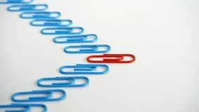 Office Paperclip Leadership Stand Out Concept. Leading red paper clip leadership and stand out concept on white background Stock Image