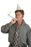 Office Party Noise Maker. A man at a party, wearing a party hat and blowing a noisemaker Royalty Free Stock Image