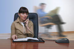 Office people. Attractive white woman in the office talking on the phone and sitting behind a big brown desk with man reading newspaper behind stock photo