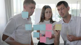 Office people look on many sticky notes on window into boardroom in Business center. Office people look on many sticky notes on window in Business center stock footage