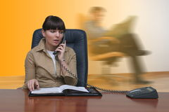 Office people - warm. Attractive white woman in the office talking on the phone and sitting behind a big brown desk with man reading newspaper behind royalty free stock photos