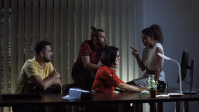Office people working at night. Multiracial office team sitting at workplace and coworking in the evening stock images