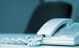 Office phone. On an empty desk, with chair in the background royalty free stock photos
