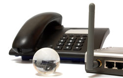 Office phone, wi-fi router and glass globe. Black office phone, gray wi-fi router and glass globe on white Stock Photography