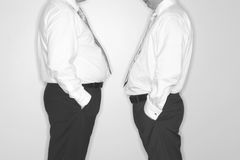 Office politics. Front view of two businessmen standing facing each other Stock Image