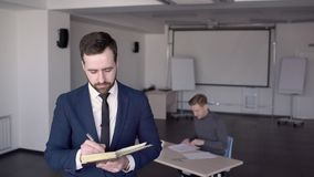 In office is a portrait of a business man who makes notes in the diary. stock video footage