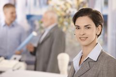 Office portrait of mid adult businesswoman. Looking at camera, smiling, coworkers in background Royalty Free Stock Images