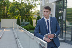 Office portrait of smiling young businessman. Standing with laptop pc Royalty Free Stock Photos