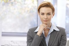 Portrait of pretty businesswoman. Office portrait of young attractive businesswoman in shirt and jacket, looking at camera Royalty Free Stock Image