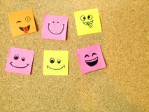 Office post it notes with various smiley happy faces on cardboard with copy space. Concept stock image