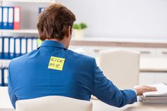 The office prank with kick me message on sticky note. Office prank with kick me message on sticky note royalty free stock photography