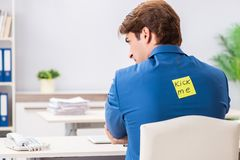 The office prank with kick me message on sticky note. Office prank with kick me message on sticky note royalty free stock photo
