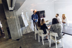 Office presentation. Group of coworkers at an office brainstorming and presentation Royalty Free Stock Photo