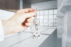 Office and realtor concept. Businessman hand holding key with house keychain on abstract concrete interior background. Office and realtor concept. 3D Rendering Royalty Free Stock Photo