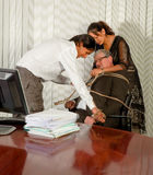 Office rebellion. Employees tying the office manager to his chair with a rope Stock Photos