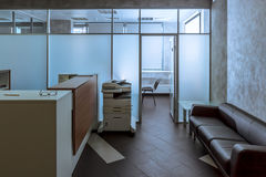 Office reception desk. Modern office entry hall with reception desk, a couch and copy-machine Stock Photography