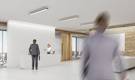 Office with reception desk and three people Stock Image