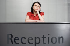 Office receptionist in a red blouse, looking bored Royalty Free Stock Photography
