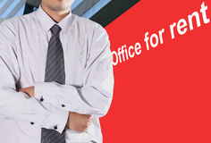 Office for rent. Cropped view of Businessman standing in front of a billboard with a red office for Rent Royalty Free Stock Photos