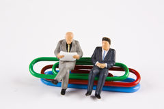 Office Report. Miniature businessmen sitting on paper clips Stock Images