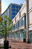 Office and Retail Buildings. A brick sidewalk in front of two-story retail space and a multi story office building with bright blue windows that reflect the sky Royalty Free Stock Image
